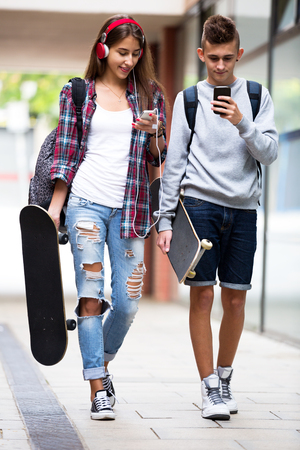 teenage guy: Smiling young friends carrying skateboards and walking through city Stock Photo