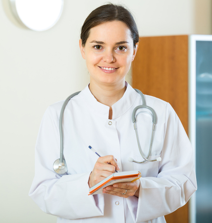 overall: Portrait of smiling female doctor in white overall in clinic