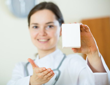 therapeutist: Female therapeutist in white overall posing with box of supplement