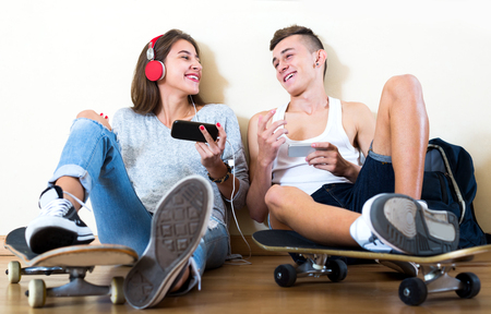 16s: Boy and his pretty girlfriend with smartphones at home