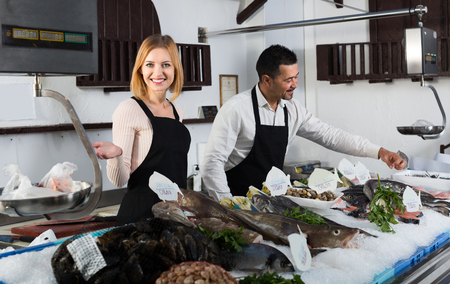 cooled: Two smiling sellers working in section of cooled fish at supermarket Stock Photo