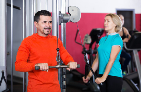 anaerobic: Adults of different age having strength training in gym