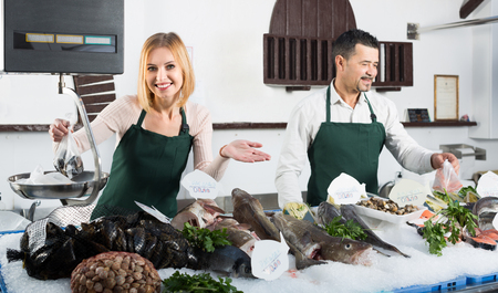 cooled: Two positive smiling sellers working in section of cooled fish at supermarket Stock Photo