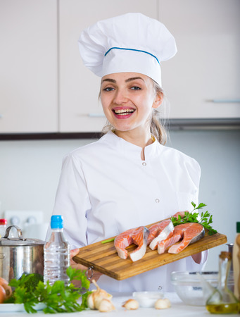 jorobado: Positive female chef holding salmon steaks on chopping board