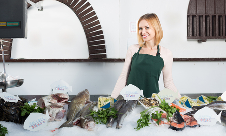 fishery products: Young blonde shopgirl near scales and display with fish