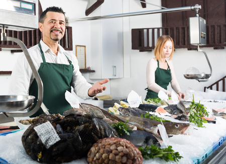 25s: Portrait of two positive sellers in aprons working in fish section of supermarket Stock Photo