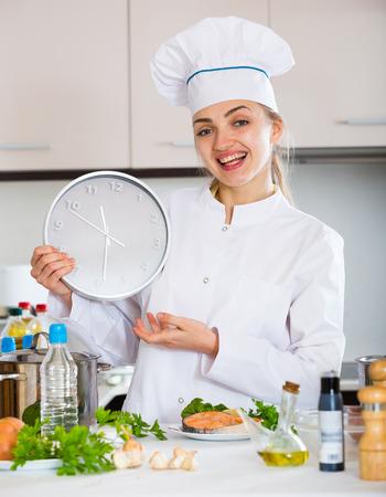 corcovado: Mujer alegre en uniforme del cocinero con el reloj y el salm�n frito