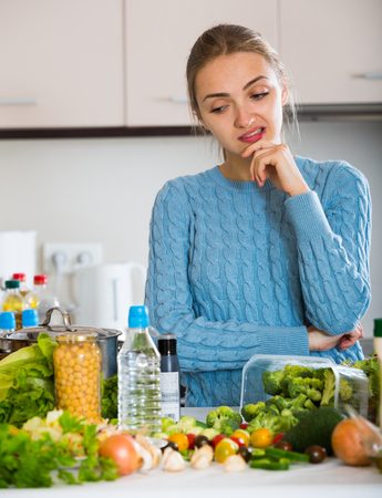 woman cooking: Confused girl in sweater thinking what to cook for lunch