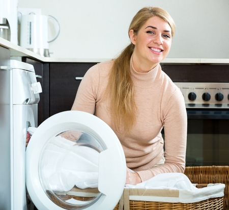 detergent: Portrait of smiling housewife satisfied with quality of washing at home