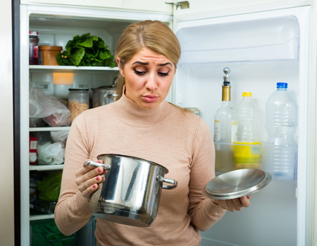loathsome: Shocked young blonde smelling foul smell of food from casserole at kitchen Stock Photo