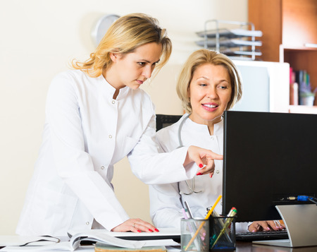 physiotherapists: Two female doctors with stethoscope working with computer together. Selective focus