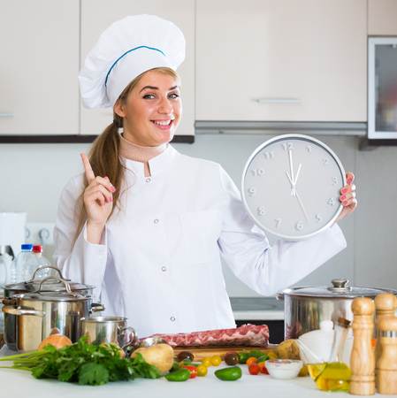 Female chef showing time needed for preparing pork ribs