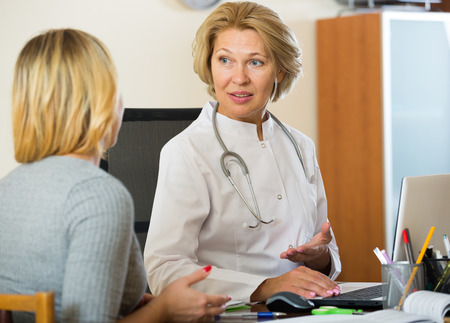Blond patient and senior therapeutist at appointment in clinic Banco de Imagens