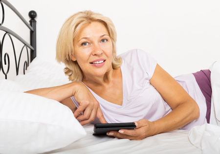 mature woman with eBook or tablet laying in  bed at home