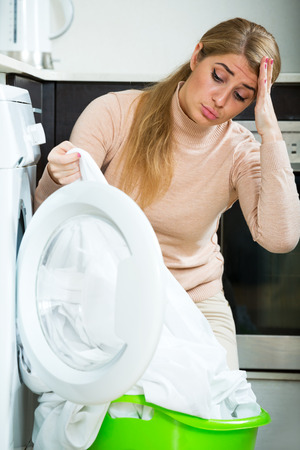 loathsome: Unhappy blonde girl with dirty white shirt near washing machine