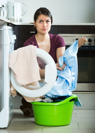 mildewed: Adult woman with musty towels after laundry at home