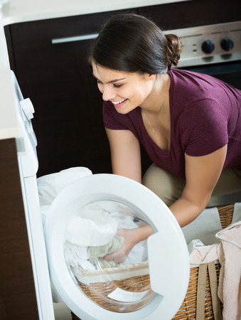 charwoman: Young positive woman with basket of sheets near washing machine indoors