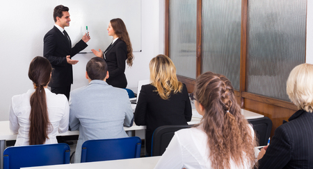 Groep volwassen studenten met een bank aan de opleiding in de business school