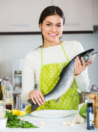 jorobado: Happy young girl in white sweater with fresh salmon fish