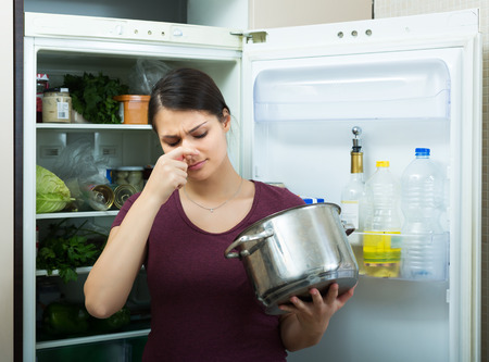 foul: Amazed brunette adult female sniffing at foul food from casserole