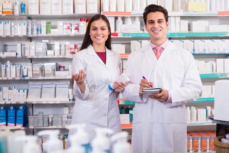 Lachend apotheker en Amerikaanse farmaceutisch technicus poseren in drogisterij Stockfoto
