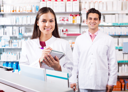 farmacy: Two positive friendly pharmacists working in modern farmacy