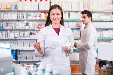 Smiling pharmacist and pharmacy technician posing in drugshop