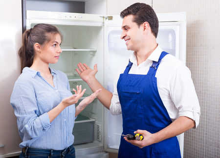 complaining: Worried woman complaining to handyman on problems with refrigerator indoors