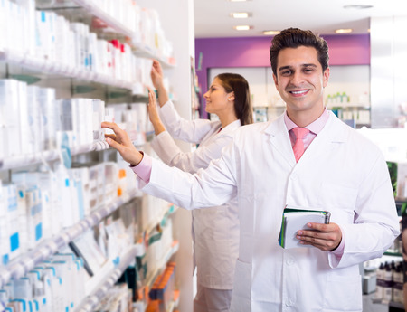 smiling doctor: Portrait of two friendly pharmacists working in modern farmacy