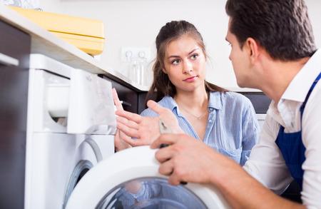 Specialist in uniform met gereedschap en huisvrouw wasmachine