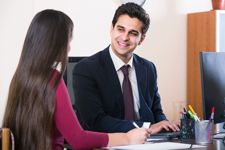 financial success: Banking agent listening to young russian customer and smiling in agency