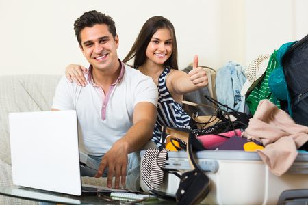 25 35: Happy young smiling couple booking tickets online and packing baggage for journey Stock Photo
