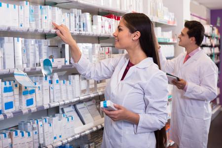 Farmacéutico sonriente y técnico de farmacia indio que presenta en la farmacia Foto de archivo