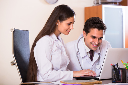 family physician: Young intern asking advice from medical tutor at clinic reception