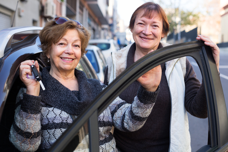 golden age: caucasian female driver in golden age standing with car key outdoor Stock Photo
