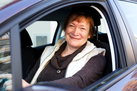 65 70: Happy mature woman sitting in new car at driver seat