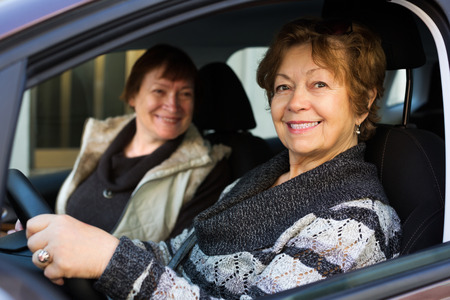 female driver: Portrait of female senior driver and her friend in car