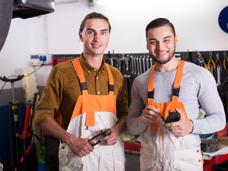 toiling: Two happy workmen toiling in the locksmiths workshop and smiling Stock Photo