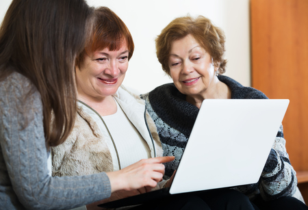 25 35: Senior women and young girl with laptop at home