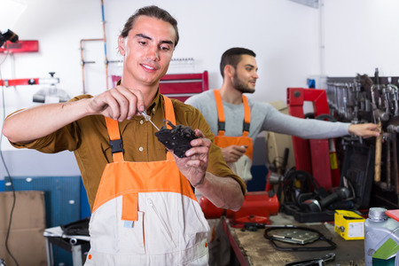 journeyman: Two cheerful repairman toiling in locksmiths workshop and smiling Stock Photo