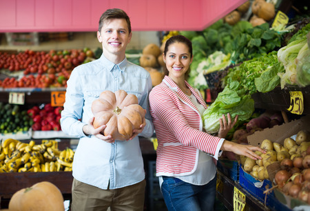 25 35: russian couple of customers buying vegetables in grocery section at supermarket