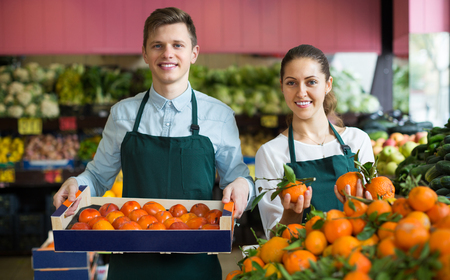 happines: Joyful supermarket workers in apron selling citrus in fruit section and smiling