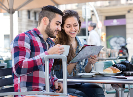 dring: Couple resting in a cafe during their trip. Man and woman examine a map and dring coffee with pastry dessert