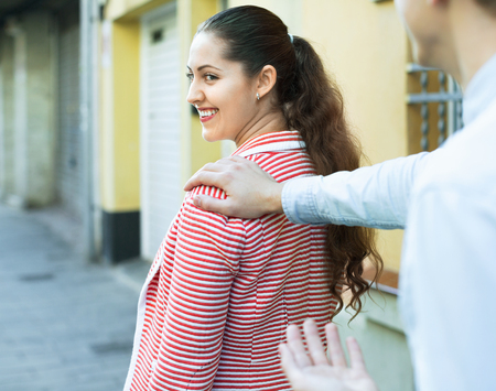 sidewalk talk: Young  man chasing pleased smiling  woman and flirting outdoor