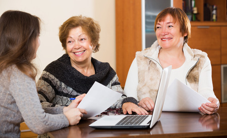 75s: Woman agent consulting cheerful elderly women in office Stock Photo