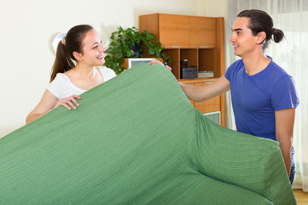 Positive smiling young couple moving furniture in room