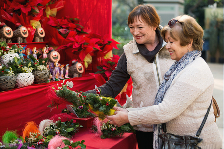 60 65 years: Happy smiling mature women selecting floral compositions at Christmas market