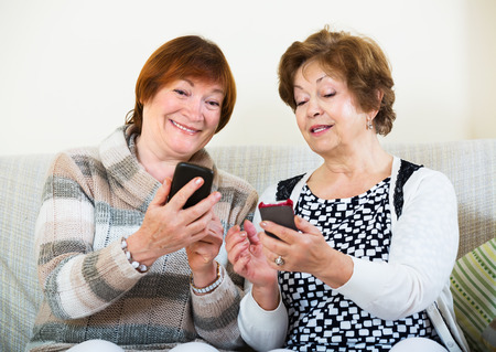 70 75: Smiling senior women sitting with smartphones in living room Stock Photo