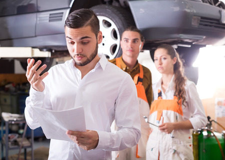 Dissatisfied male client duping by troubleshooters at auto service