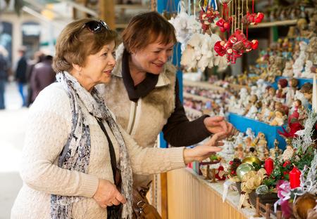 70 75 years: Positive senior women walking on the Christmas Fair and chosen decoration